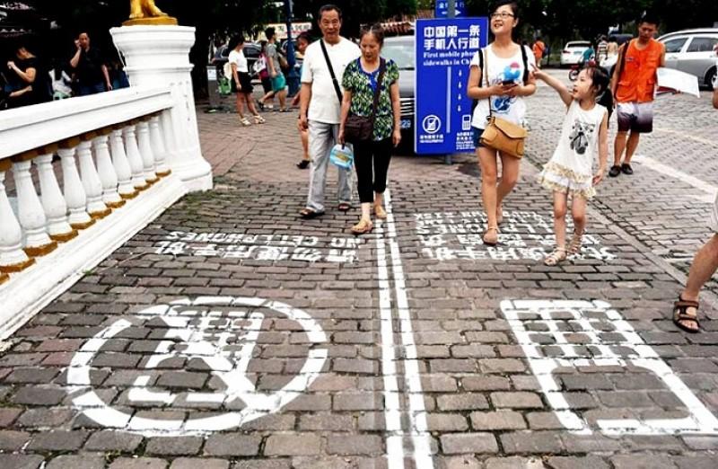 China crea el primer carril peatonal para los que siempre ven su celular