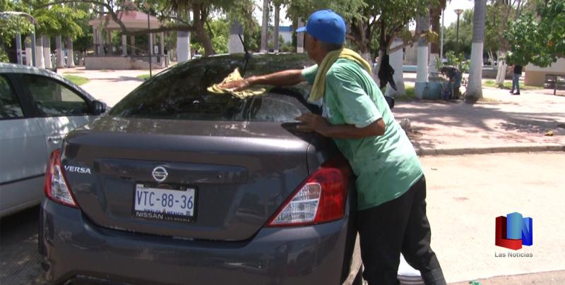 En Cajeme, los lavacarros un oficio en las plazas