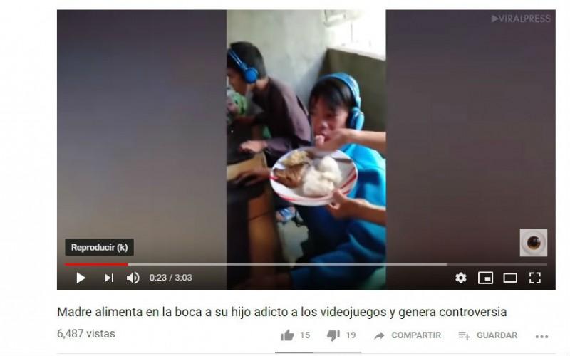 ¡A donde vamos a parar! madre alimenta en la boca a su hijo mientras él juega vídeo juegos