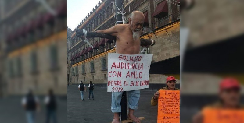 Hombre se 'crucifica' frente a Palacio Nacional para hablar con AMLO