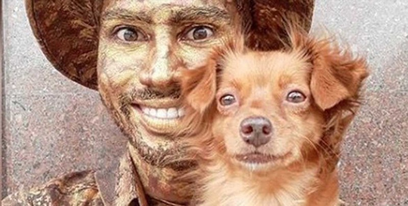 Perro pretende ser estatua junto con su dueño