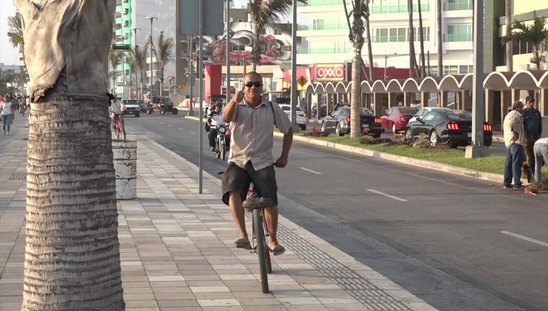 De reversa, en su bicicleta, recorre la ciudad