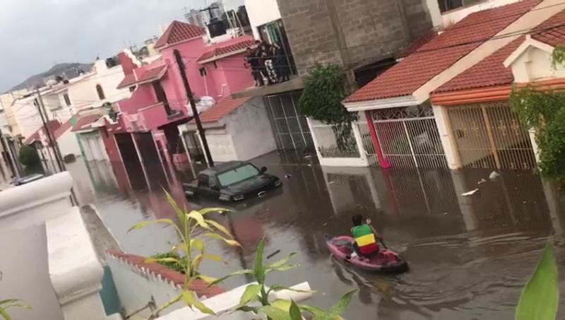 Jóvenes aprovechan lluvia e inundación para navegar en Kayak e improvisar alberca
