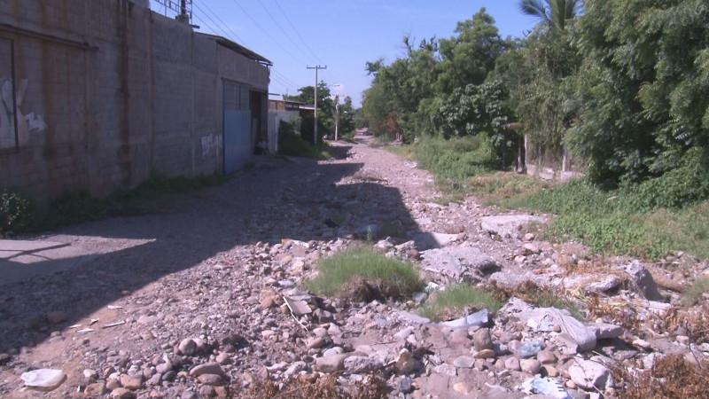 Calle Adalberto Tejeda llena de piedras y basura