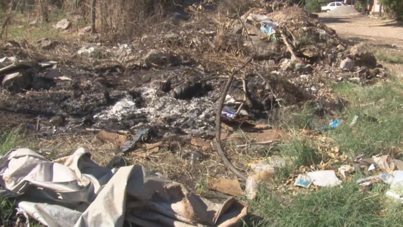 Basura y escombro invade calle en La Huizaches