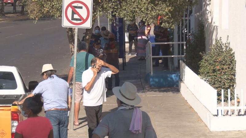 Persisten largas filas de personas en las afueras de las instituciones bancarias