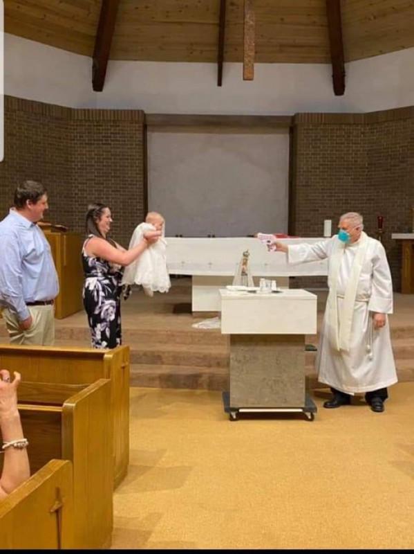 Padre utiliza pistola de agua para bautizar a un bebé a la distancia