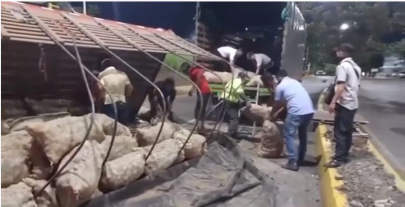 Trailer con comida se voltea y en vez de saquearlo, vecinos ayudan a juntarla
