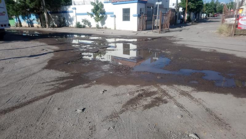Calle de los peninos con aguas negras y llena de baches
