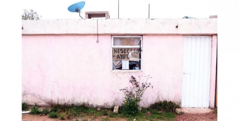 """""""Necesito su ayuda"""": familia entera se contagia de Covid-19 y piden apoyo por carteles en la ventana"""